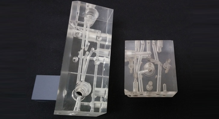Example manifolds machined from clear acrylic in order to demonstrate internal complexities.